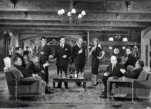 darrieux, duvivier, ventura, blier, dalban, iverbel, meurisse, frankeurDe Julien Duvivier, j'avais été intrigué par Un carnet de bal, film d'avant-guerre (1937) dans lequel une femme qui avait fait un mauvais mariage reprenait contact avec les hommes qui l'avaient courtisée. De rencontre en rencontre, le film traçait le portrait d'une génération d'hommes d'avant-guerre peu flatteuse. Empreint d'un ton assez pessimiste, il semblait prémonitoire des événements à venir. Pourvu d'excellents acteurs, dont Louis Jouvet, Fernandel ou Raimu, il témoignait des talents de Duvivier à utiliser de grandes figures du cinéma français et à leur faire jouer des rôles ambigus, ce qu'il reproduit dans le prenant Marie-Octobre, sorti en 1959. Huis-clos efficace Plus de vingt ans après, il met donc en scène dans un huis-clos efficace la star Danièle Darrieux et dix grands acteurs que sont Paul Meurisse, Lino Ventura, Serge Reggiani, Noël Roquevert, Paul Frankeur, Bernard Blier, Robert Dalban, Paul Guers, Daniel Ivernel et Jeanne Fusier-Gir. La belle Marie-Hélène dite Marie-Octobre (Darrieux) invite dans son château les anciens membres du réseau de résistance Vaillance à se souvenir de leur chef Castille, assassiné par la gestapo. Ils sont tous venus, tranquilles, prospères, pour s'entendre dire par leur hôtesse que l'un d'eux a donné Castille aux allemands quinze ans auparavant. La soirée aboutira à découvrir le coupable. Tout se passe dans le salon du château de Marie-Octobre et cet espace vaste comme une scène de théâtre permet à Duvivier d'utiliser toutes les perspectives possibles pour mettre en scène ses nombreux personnages. A l'instar du filmage d'un match de catch, que l'on voit sur le téléviseur du salon allumé par Marinval (Frankeur), la caméra joue avec les corps de ses acteurs, captant les face à face, les uns contre tous, les visages soudain chargés de culpabilité. Pour cela, il alterne les gros plans sur les visages, plans rapprochés ou plans d'ensemble, dans un montage dy